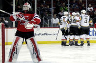 Vegas Golden Knights players, right, celebrate a goal by right wing Alex Tuch (89) on New Jersey Devils goaltender Cory Schneider, left, during the first period of an NHL hockey game, Friday, Dec. 14, 2018, in Newark. (AP Photo/Julio Cortez)
