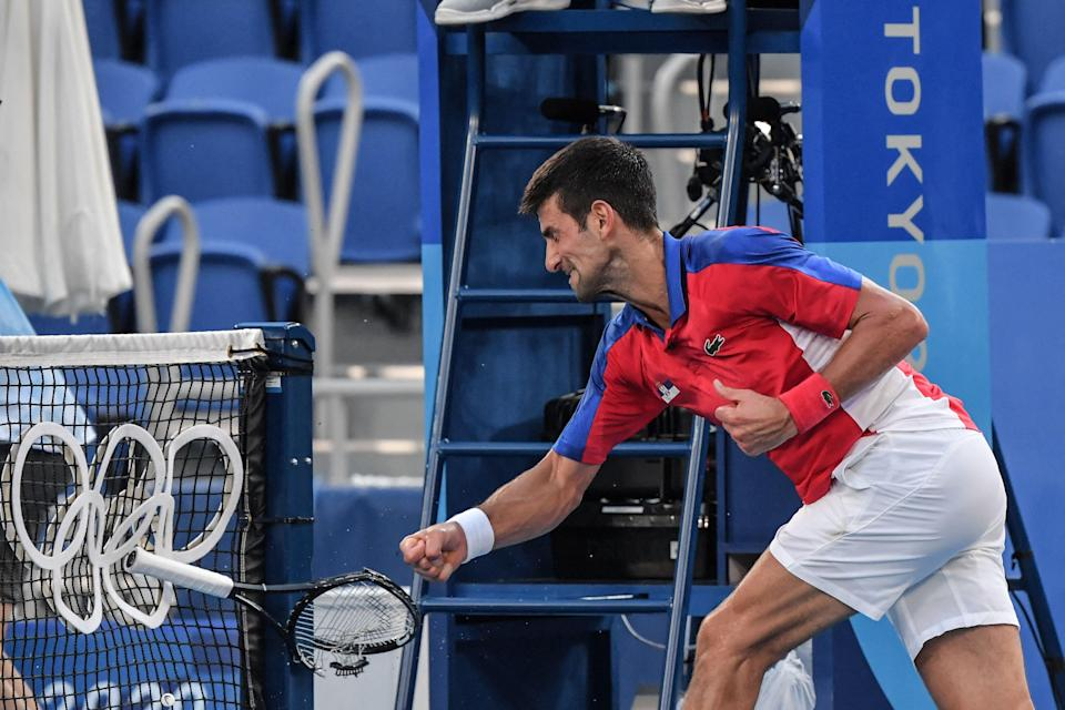 Djokovic smashes a racket after throwing one into the stands (AFP via Getty Images)