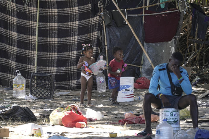 Migrant children play near a man in an encampment under the Del Rio International Bridge where migrants, many from Haiti, have been staying after crossing the Rio Grande, Thursday, Sept. 23, 2021, in Del Rio, Texas. (AP Photo/Julio Cortez)