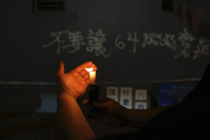 A protester lights candles to mark the anniversary of the military crackdown on a pro-democracy student movement in Beijing, outside the Victoria Park in Hong Kong, Friday, June 4, 2021. A member of the committee that organizes Hong Kong's annual candlelight vigil for the victims of the Tiananmen Square crackdown was arrested early Friday on the 32nd anniversary. (AP Photo/Kin Cheung)