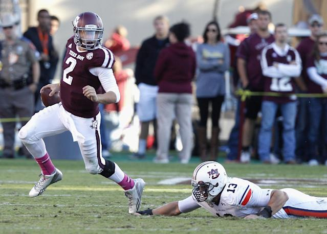 Texas A&M quarterback Johnny Manziel (2) avoids the grasp of Auburn defensive end Craig Sanders (13) in the third quarter during an NCAA college football game Saturday, Oct. 19, 2013, in College Station, Texas. Auburn won 45-41. (AP Photo/Bob Levey)