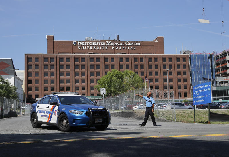 A Westchester Medical Center security guard directs traffic as a Westchester County police car pulls out of the drive to the main entrance of the hospital, Wednesday, Aug. 8, 2018, in Valhalla, N.Y. A man shot a female patient and then killed himself at the suburban New York hospital Wednesday, police said.(AP Photo/Julie Jacobson)