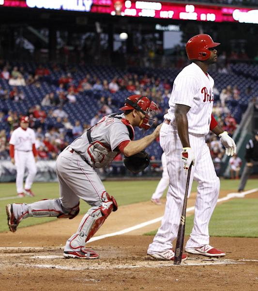 Philadelphia Phillies' Ryan Howard, right, gets tagged out by Cincinnati Reds' catcher Devin Mesoraco, left, after striking out and stranding two runners during the third inning of a baseball game, Friday, May 16, 2014, in Philadelphia. (AP Photo/Chris Szagola)