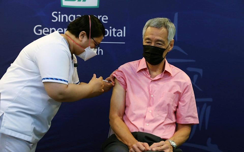 Prime Minister Lee Hsien Loong receives a booster shot - Reuters