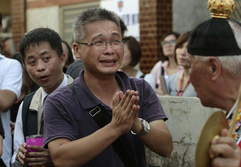 A relative of a victim killed in the TransAsia Airways Flight GE222 crash prays at a makeshift altar at the crash site on the outlying island of Penghu, Taiwan, Thursday, July 24, 2014. Stormy weather on the trailing edge of Typhoon Matmo was the likely cause of the plane crash that killed more than 40 people, the airline said Thursday. (AP Photo/Wally Santana)
