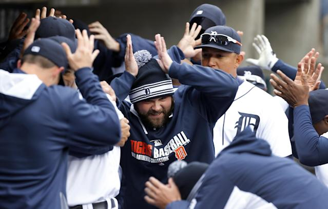 Detroit Tigers players including Joba Chamberlain dance in the dugout before a baseball against the Baltimore Orioles in Detroit Friday, April 4, 2014. (AP Photo/Paul Sancya)