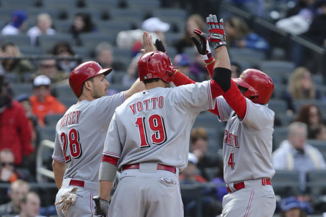 Cincinnati Reds second baseman Brandon Phillips (4) celebrates with left fielder Chris Heisey (28) and first baseman Joey Votto (19) after hitting a two-run home run in the seventh inning of their baseball game against the New York Mets at Citi Field, Saturday, April 5, 2014, in New York. (AP Photo/John Minchillo)