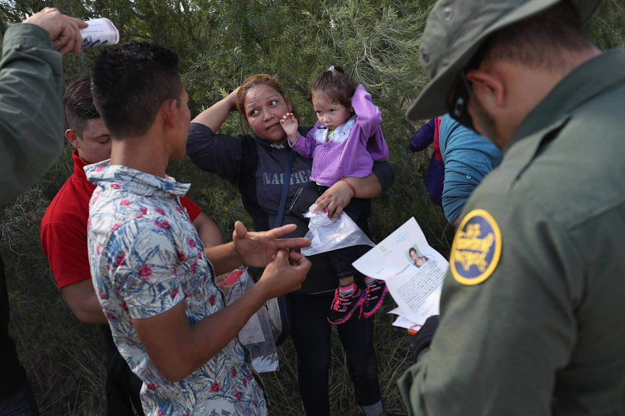 U.S. Border Patrol agents ask a group of Central American asylum seekers to remove hair bands and wedding rings before taking them into custody in June 2018 near McAllen, Texas. (Photo: John Moore/Getty Images)