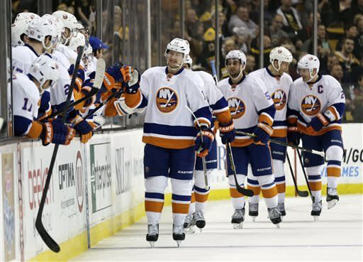 New York Islanders center Josh Bailey, center, is congratulated by teammates after his goal against Boston Bruins goalie Tuukka Rask during the second period of an NHL hockey game in Boston, Thursday, April 11, 2013. (AP Photo/Charles Krupa)