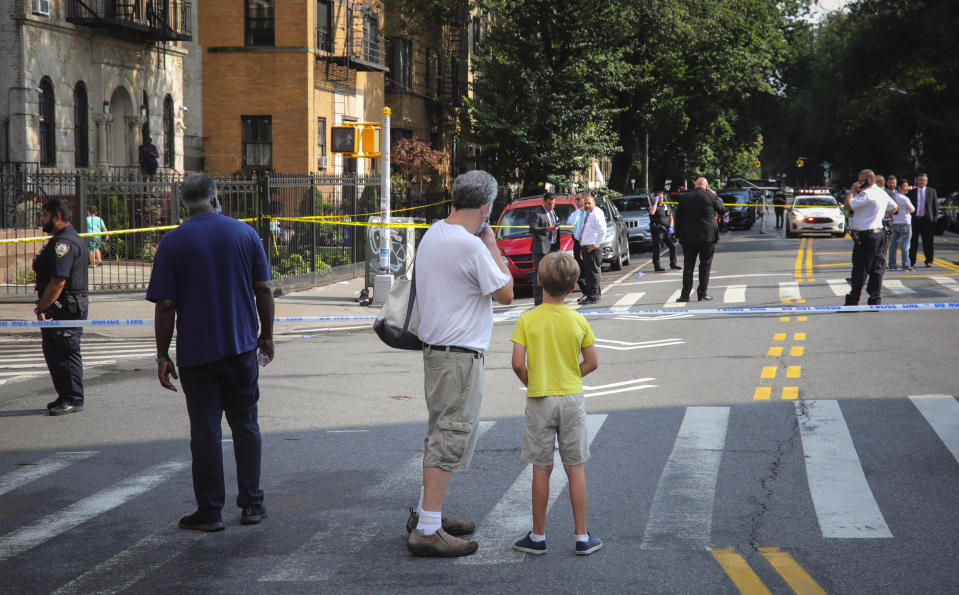FILE - Bystanders watch as police investigate the scene of a multiple shooting near Brooklyn's Prospect Park, Wednesday Aug. 19, 2020, in New York. Police report an 18-year-old male died from gunshot wounds to the chest and arms and a 33-year-old male with a gunshot wound to the abdomen is in stable condition. Police recorded 280 killings through Aug. 23, up from 208 during the same period last year. (AP Photo/Bebeto Matthews)