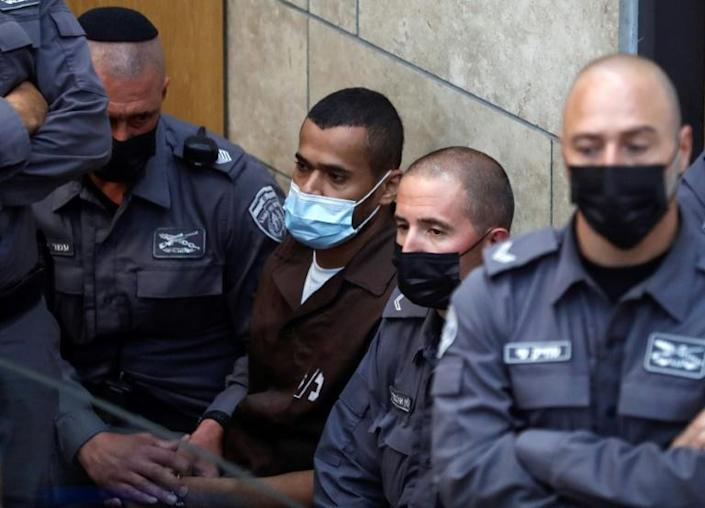 Palestinian Munadel Infeiat, one of six prisoners who had tunnelled out of Israel's high security Gilboa prison is surrounded by Israeli police officers as he appears at the magistrates' court in the northern Israeli city of Nazareth (AFP/Ahmad GHARABLI)
