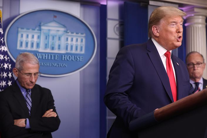 U.S. President Donald Trump addresses the coronavirus task force daily briefing as as National Institute of Allergy and Infectious Diseases Director Anthony Fauci listens at the White House in Washington, U.S., March 24, 2020. REUTERS/Jonathan Ernst