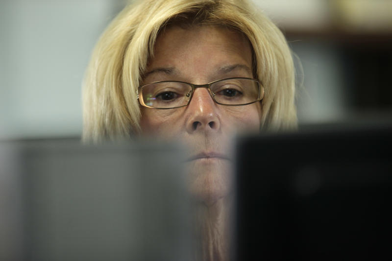 Library clerk Jane Stahl works on a computer at a San Diego Public Library Friday, June 8, 2012, in San Diego. Stahl has worked for the city as a librarian for seven years. Voters in San Diego and San Jose overwhelmingly approved ballot measures last week to roll back municipal retirement benefits - and not just for future hires but for current employees. (AP Photo/Gregory Bull)
