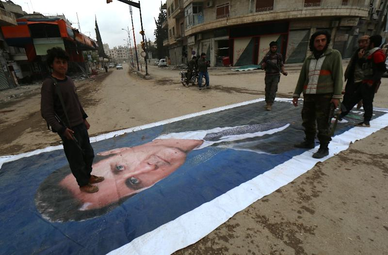 Islamist fighters stand on a huge portrait of Syrian President Bashar al-Assad after capturing Idlib, on March 29, 2015 (AFP Photo/Zein Al-Rifai)
