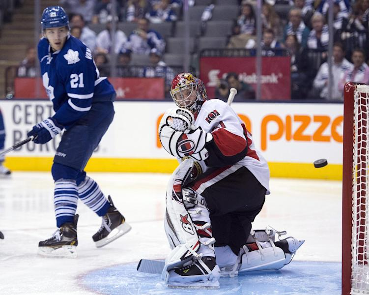 Toronto Maple Leafs' James van Riemsdyk (21) watches the puck as it passes Ottawa Senators goaltender Craig Anderson but misses the net during second-period NHL hockey game action in Toronto, Saturday, Oct. 5, 2013. (AP Photo/The Canadian Press, Frank Gunn)