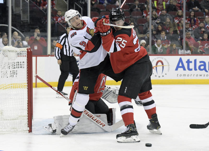 New Jersey Devils defenseman Mirco Mueller (25) checks Ottawa Senators right wing Bobby Ryan (9) during the first period of an NHL hockey game Wednesday, Nov. 13, 2019, in Newark, N.J. (AP Photo/Bill Kostroun)
