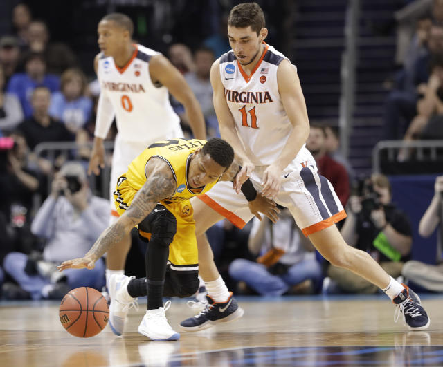 UMBC's Jairus Lyles (10) loses the ball as Virginia's Ty Jerome (11) defends during the first half of a first-round game in the NCAA men's college basketball tournament in Charlotte, N.C., Friday, March 16, 2018. (AP Photo/Gerry Broome)