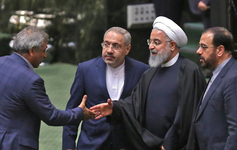Iranian lawmakers greet President Hassan Rouhani (2nd-R)  in the capital Tehran on February 4, 2019