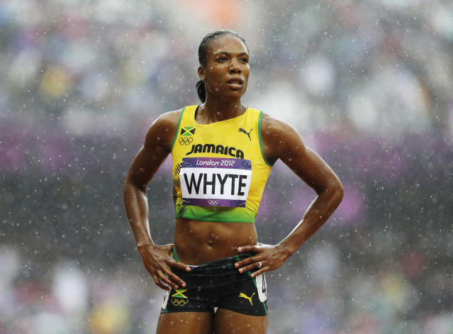Jamaica's Rosemarie Whyte stands in the pouring rain during a women's 400-meter heat during the athletics in the Olympic Stadium at the 2012 Summer Olympics, London, Friday, Aug. 3, 2012. (AP Photo/Anja Niedringhaus)