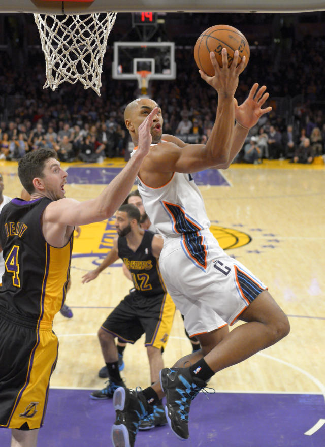 Charlotte Bobcats guard Gerald Henderson, right, puts up a shot as Los Angeles Lakers forward Ryan Kelly defends during the first half of an NBA basketball game, Friday, Jan. 31, 2014, in Los Angeles. (AP Photo/Mark J. Terrill)