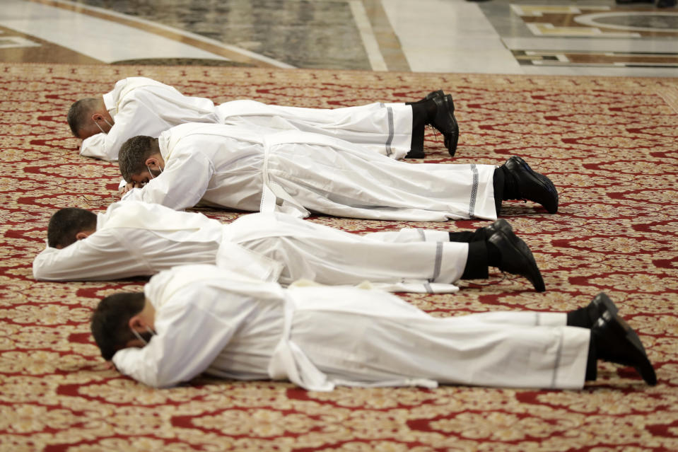 New priests lie face down on the ground during their ordination ceremony lead by Pope Francis, inside St. Peter's Basilica, at the Vatican, Sunday, April 25, 2021. (AP Photo/Andrew Medichini)