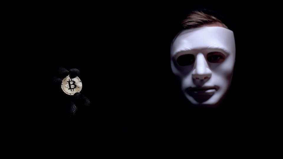 Man showing bitcoin, fearful anonymous mask on face, cyber attack, robbery