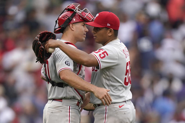 Philadelphia Phillies' J.T. Realmuto, left, celebrates with Ranger Suarez after they defeated the Boston Red Sox in a baseball game, Sunday, July 11, 2021, in Boston. (AP Photo/Steven Senne)