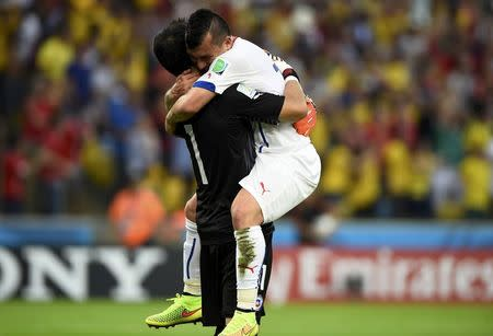 Chile's Gary Medel (R) hugs teammate Claudio Bravo after Chile's Eduardo Vargas scored the team's first goal during their 2014 World Cup Group B soccer match against Spain at the Maracana stadium in Rio de Janeiro June 18, 2014. REUTERS/Dylan Martinez
