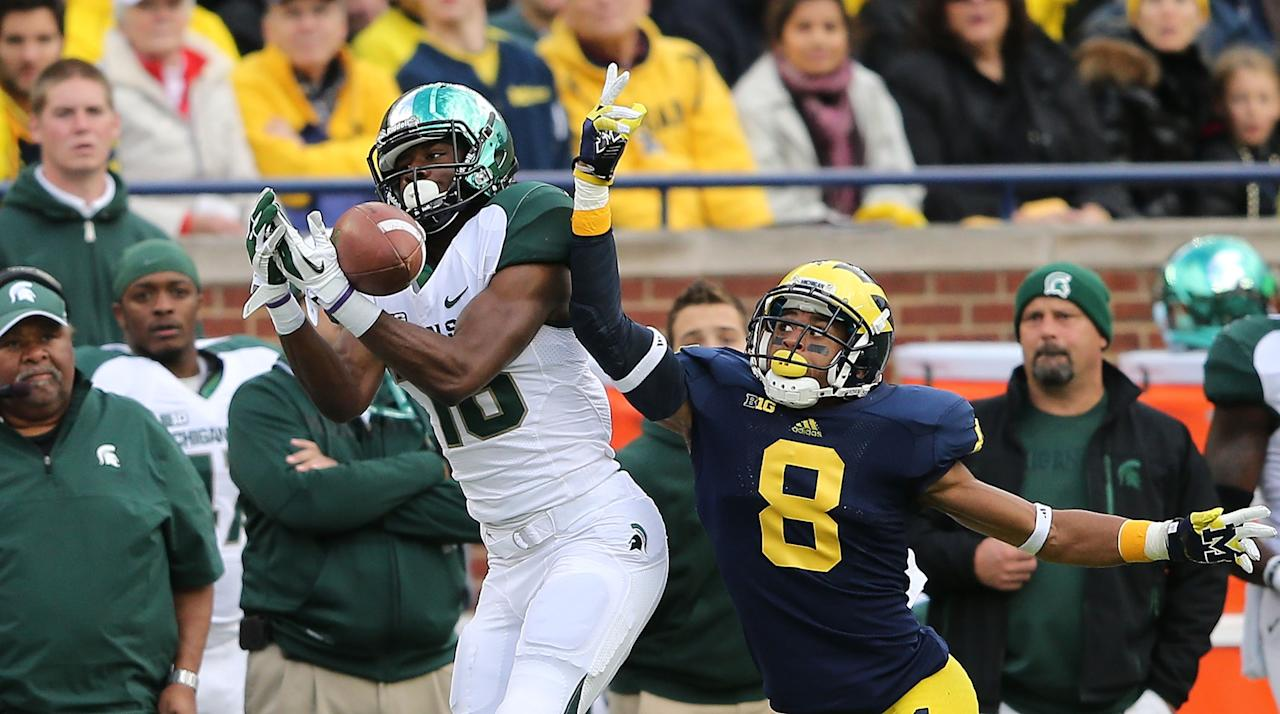 ANN ARBOR, MI - OCTOBER 20:  Russell Bellomy #8 of the Michigan Wolverines defends Aaron Burbridge #16 of the Michigan State Spartans during the game at Michigan Stadium on October 20, 2012 in Ann Arbor, Michigan. The Wolverines defeated the Spartans 12-10.  (Photo by Leon Halip/Getty Images)
