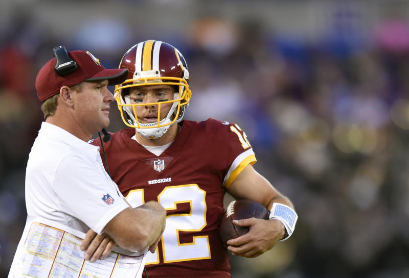 Washington Redskins head coach Jay Gruden, left, speaks with quarterback Colt McCoy in the first half of a preseason NFL football game against the Baltimore Ravens, Thursday, Aug. 10, 2017, in Baltimore. (AP Photo/Gail Burton)