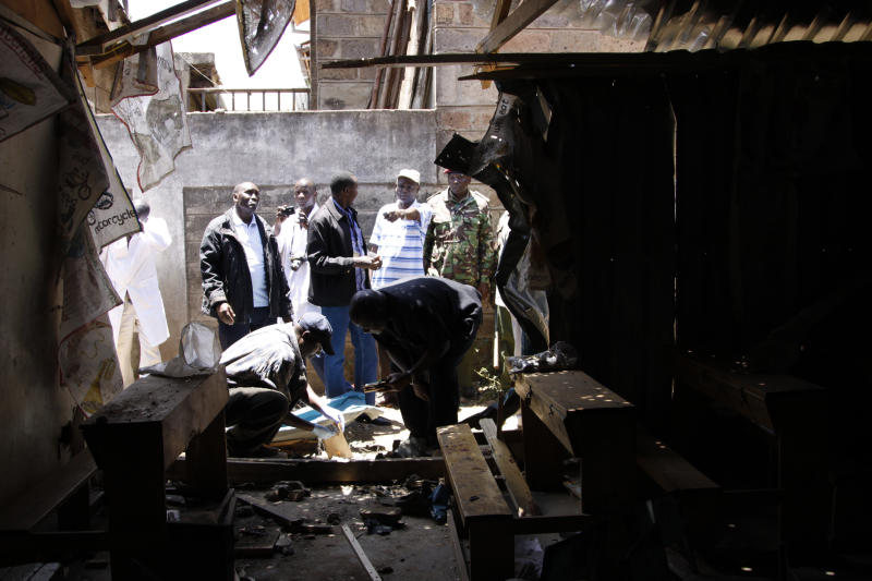 Plain clothed Kenyan police officers inspect the damage following an explosion which devastated abuilding in Nairobi, Kenya, Sunday. Sep, 30, 2012. The acting police chief in Kenya's capital says an explosive device set off in a Sunday school class killed one child and seriously wounded three. (AP Photo/Khalil Senosi)