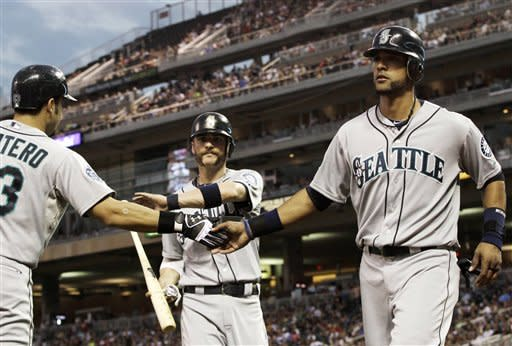 Seattle Mariners' Jesus Montero, left, greets Brendan Ryan, center, and Franklin Gutierrez, right, after they scored on a double by Kyle Seager in the third inning of a baseball game, Tuesday, Aug. 28, 2012, in Minneapolis. (AP Photo/Jim Mone)