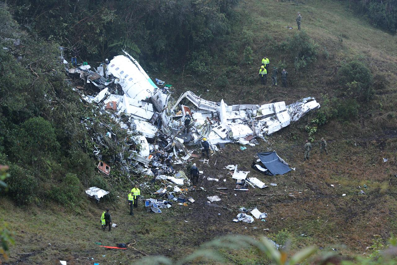 <p>Police officers and rescue workers search for survivors around the wreckage of a chartered airplane that crashed in La Union, a mountainous area outside Medellin, Colombia, Tuesday, Nov. 29, 2016. (AP Photo/Luis Benavides) </p>