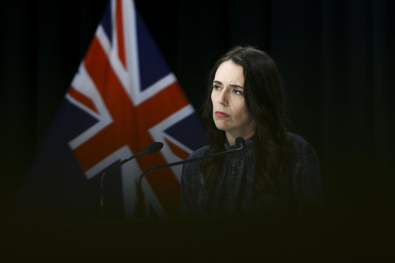 Jacinda Ardern pictured in all black in front of a New Zealand flag.