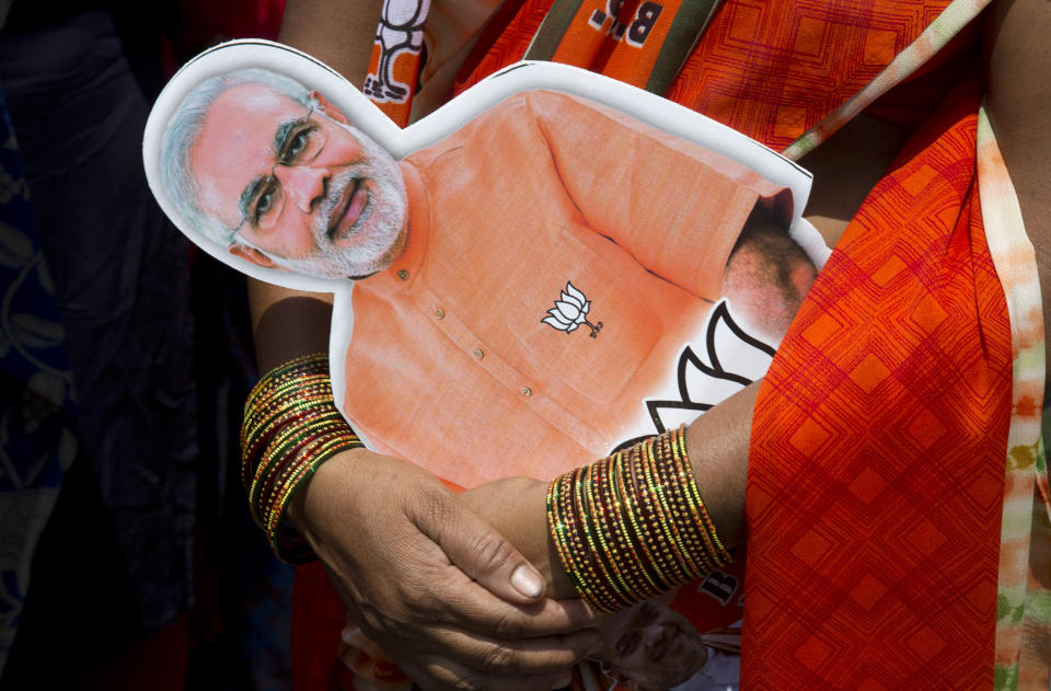 A BJP activist holds a photograph of Prime Minister Narendra Modi as she participates in an election campaign rally in Hyderabad.