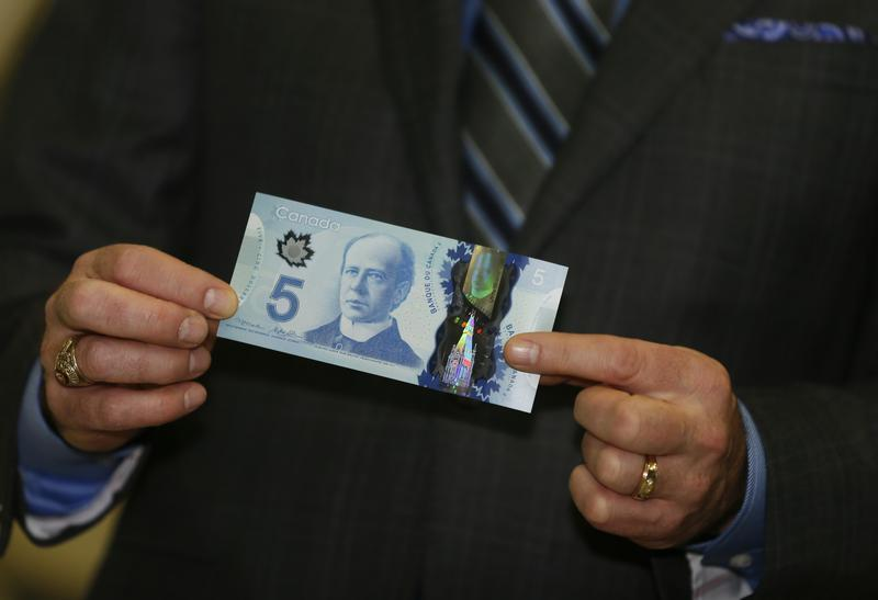 Bank of Canada Governor Poloz presents the new Canadian five dollar bill made of polymer that is entering circulation today, at the Canadian Space Agency in St. Hubert