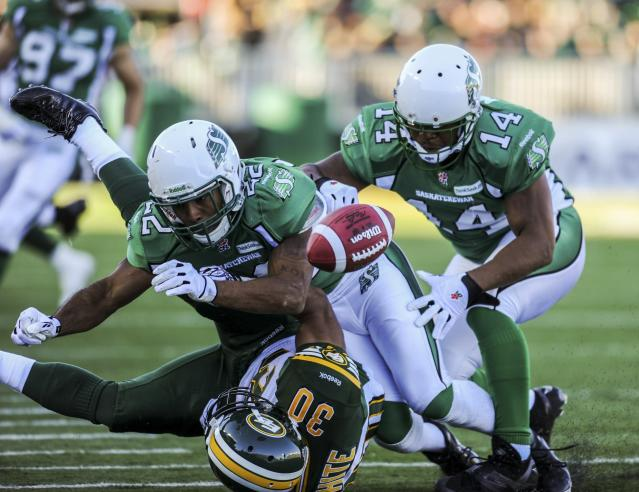 Saskatchewan Roughriders linebacker Diamond Ferri and defensive back Prince Miller (R) bring down Edmonton Eskimos running back John White (bottom) during the second half of their CFL football game in Regina, Saskatchewan October 12, 2013. REUTERS/Matt Smith (CANADA - Tags: SPORT FOOTBALL)