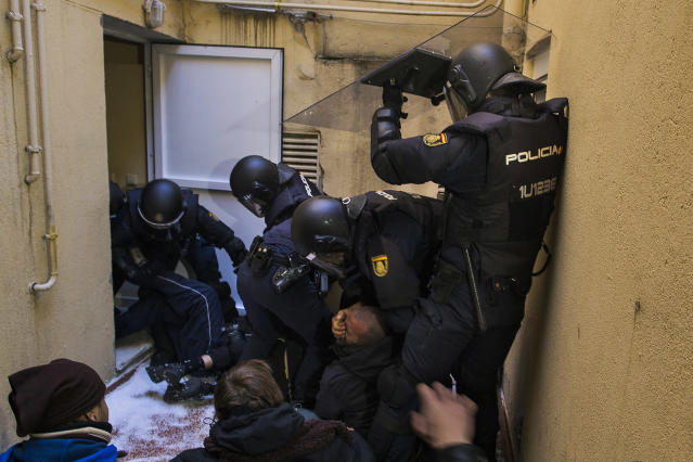 <p>Riot police grab the face of a housing rights activist as he tries to stop Umberto Jimenez's eviction in Madrid, Feb. 9, 2015. (AP Photo/Andres Kudacki) </p>