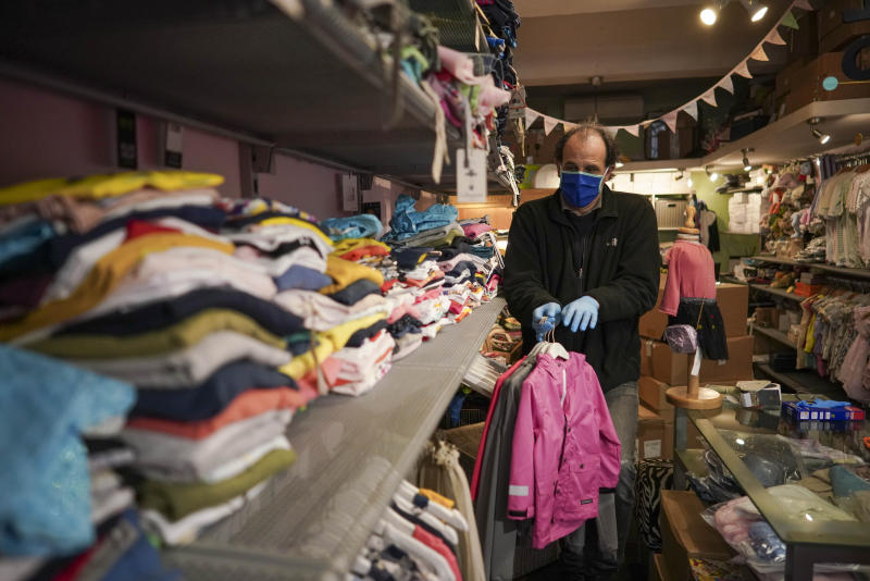 Gianfranco Mandas wears a face mask as he sorts out clothing in his children's clothes shop after it was allowed to opens following restriction measures to contain the spread of Covid-19, in Rome, Tuesday, April 14, 2020. In Italy, bookstores, stationary stores and shops selling baby clothes and supplies were allowed to open nationwide on Tuesday, provided they could maintain the same social-distancing and sanitary measures required in supermarkets. The new coronavirus causes mild or moderate symptoms for most people, but for some, especially older adults and people with existing health problems, it can cause more severe illness or death. (AP Photo/Andrew Medichini)