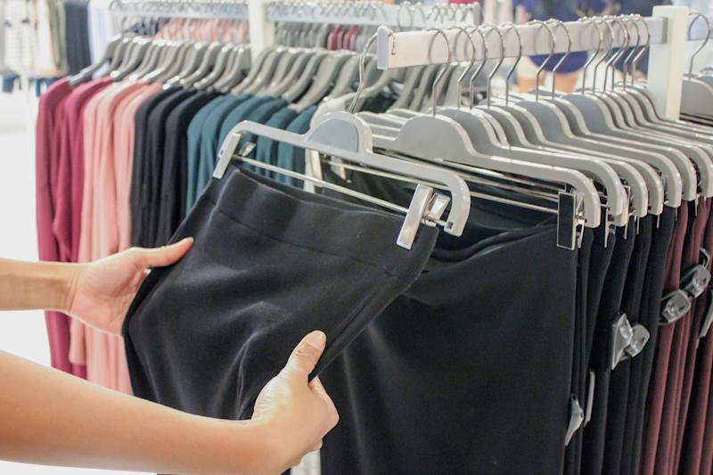 Close up females hand holding and touching a black jersey fabric legging. The young women shopping sports clothing