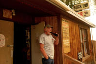 Dave Ferner drinks a beer while watching multiple homes burn in central Doyle, Calif., as the Sugar Fire, part of the Beckwourth Complex Fire, tears through town on Saturday, July 10, 2021. Ferner said he saved his home using a bulldozer earlier in the day. (AP Photo/Noah Berger)