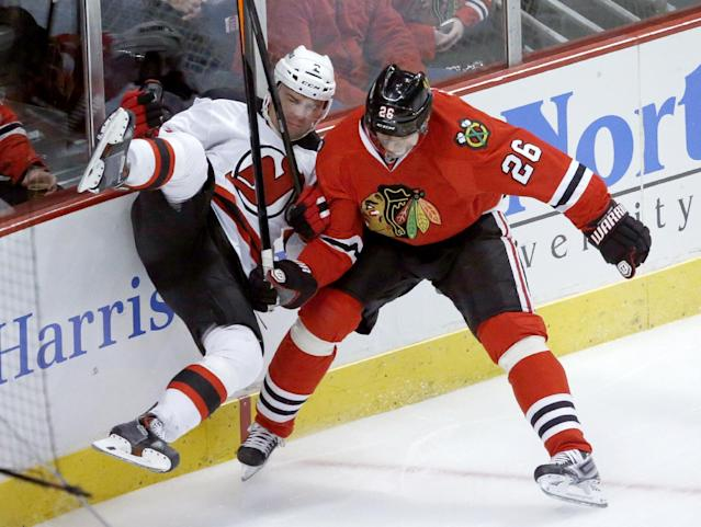 Chicago Blackhawks center Michal Handzus (26) checks New Jersey Devils defenseman Marek Zidlicky along the boards during the first period of an NHL hockey game Monday, Dec. 23, 2013, in Chicago. (AP Photo/Charles Rex Arbogast)