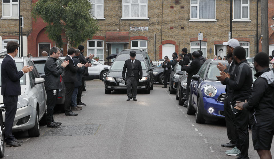 Grass roots soccer referees form a guard of honour and clap for the hearse carrying Jermaine Wright, a referee of the Hackney Marshes grassroots football league who died of COVID-19 in London, Thursday, June 11, 2020. The deadly coronavirus has killed thousands of people in Britain, but each death is not just a number, and is deeply personal for each family, group of colleagues and friends.(AP Photo/Frank Augstein)