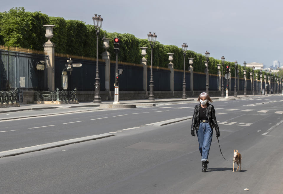 A woman wears a mask to protect against the spread of the coronavirus walks his dog at the empty Rivoli street along the Tuileries Garden in Paris, Saturday, April 25, 2020. France continues to be under an extended stay-at-home order until May 11 in an attempt to slow the spread of the COVID-19 pandemic. (AP Photo/Michel Euler)