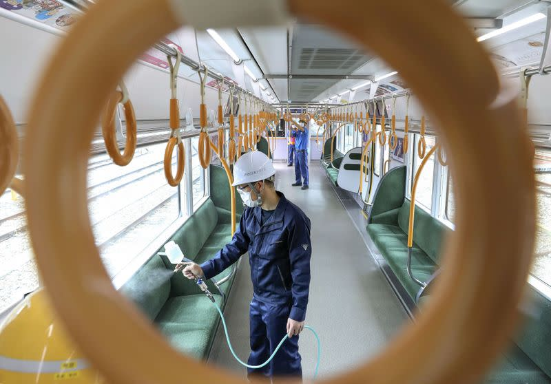 A worker sprays an antiviral liquid inside a train amid the coronavirus disease (COVID-19) outbreak in Osaka, Japan