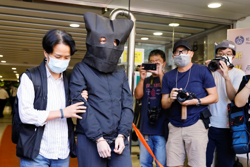 Police escort one of five suspects, detained on suspicion of publishing and distributing seditious material, in Hong Kong
