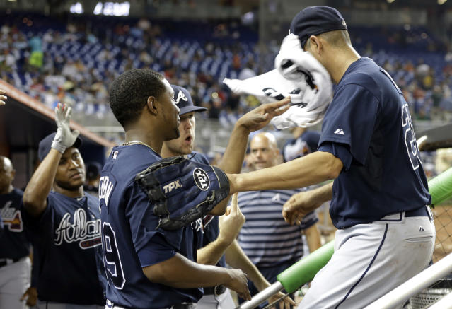 Atlanta Braves relief pitcher Luis Avilan, right, has a towel thrown at his face as he is met in the dugout by starting pitcher Julio Teheran, right, after pitching in the seventh inning during a baseball game against the Miami Marlins, Tuesday, Sept. 10, 2013 in Miami. The Braves defeated the Marlins 4-3. (AP Photo/Lynne Sladky)