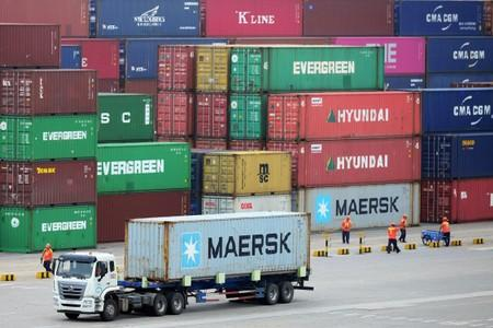 FILE PHOTO: Truck transports a container at a port in Qingdao, Shandong