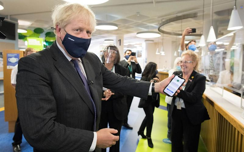 Prime Minister Boris Johnson scans his NHS Coronavirus App at Uxbridge Library during a walkabout where he met shoppers and shopkeepers in his constituency of Uxbridge, west London - Stefan Rousseau/PA Wire