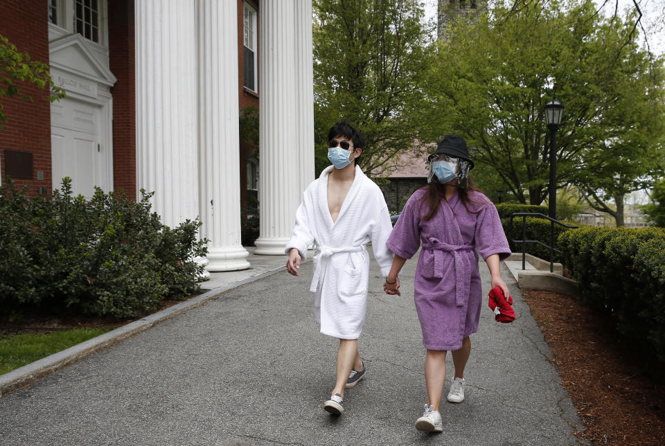 BOSTON, MA - MAY 17: Graduating Tufts Seniors Seungyoon Kim, left, and Georgette Koo walk on campus in Medford, MA on May 17, 2020. They had no reason to dress up today since their Commencement was cancelled due to COVID-19 so they strolled through campus in their bathrobes instead of a cap and gown. (Photo by Jessica Rinaldi/The Boston Globe via Getty Images)